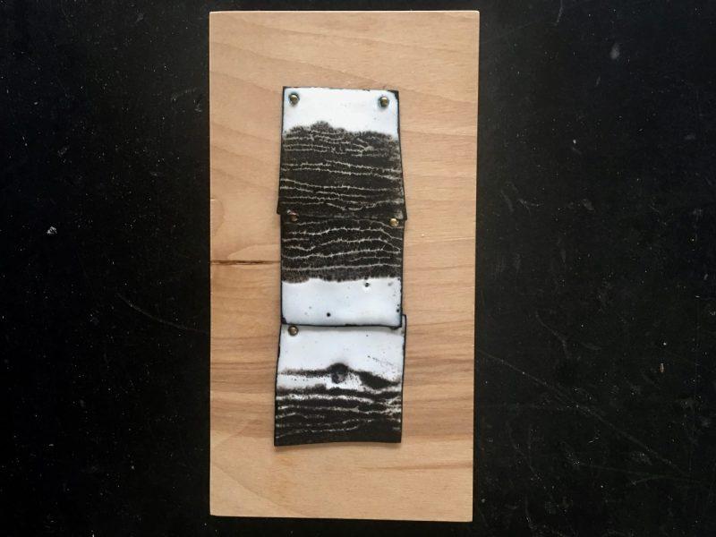 3 black and white copper enamel tiles on board